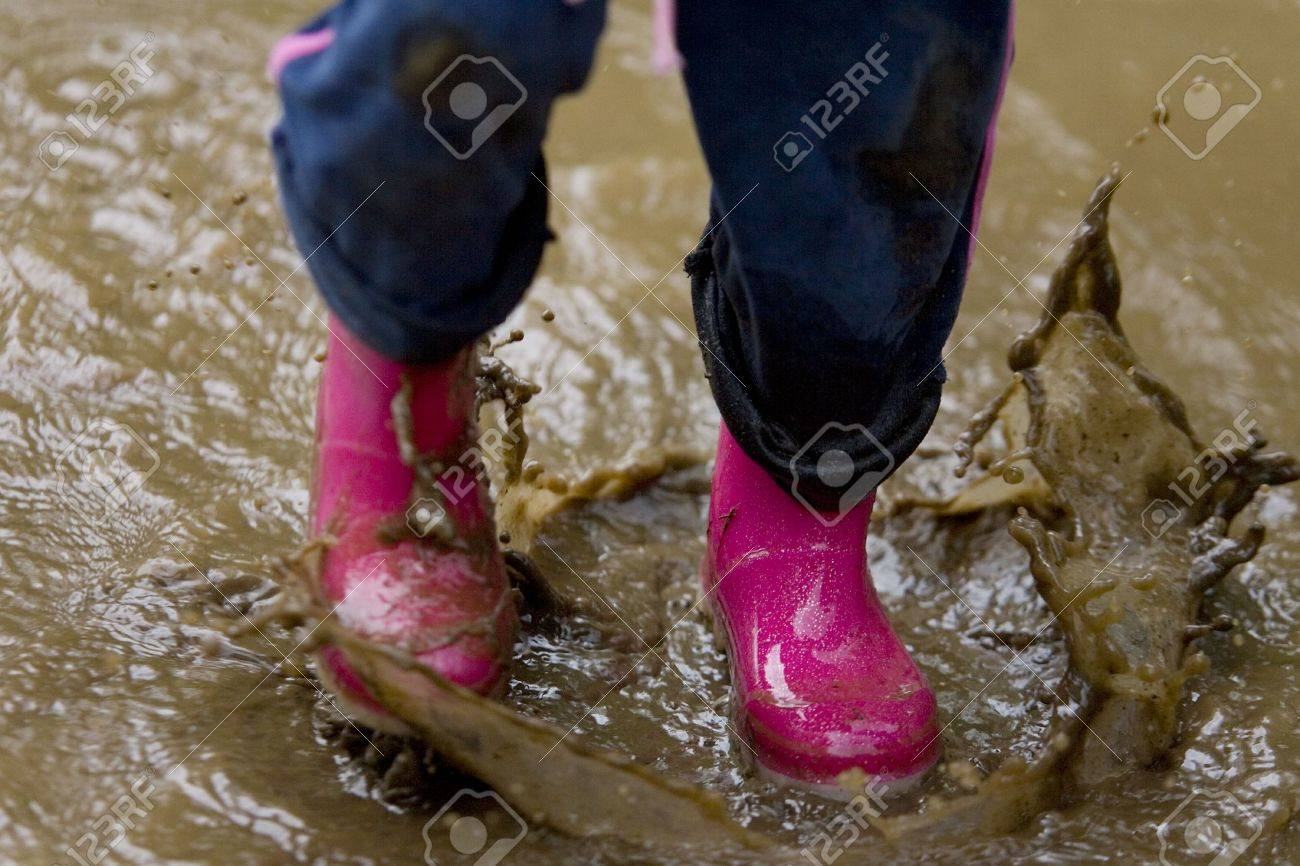 A Little Girls Pink Boots Splashing In A Muddy Puddle Stock Photo ...