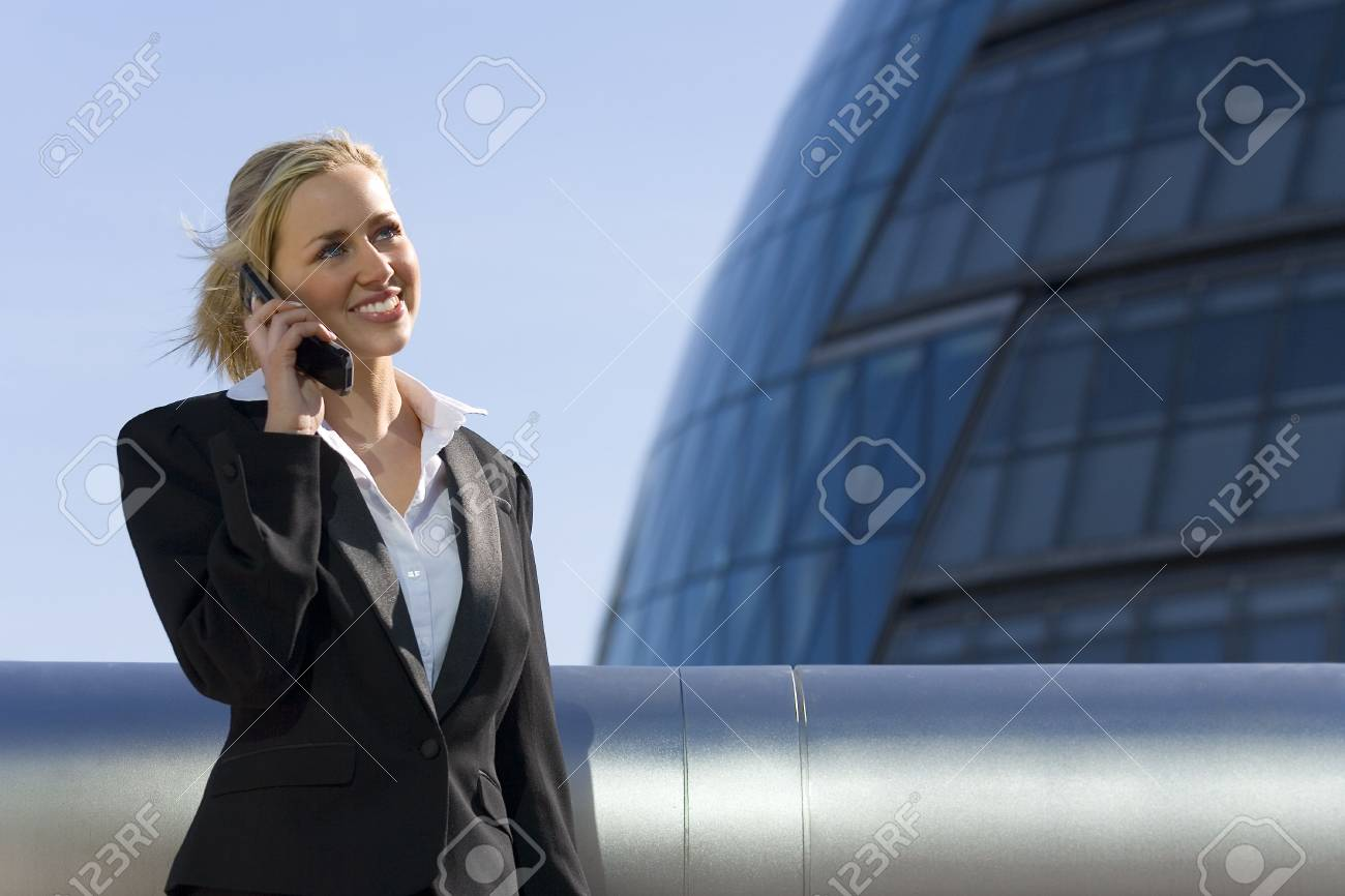 A beautiful young blonde executive using a mobile phone in a hi-tech surrounding. Stock Photo - 901257