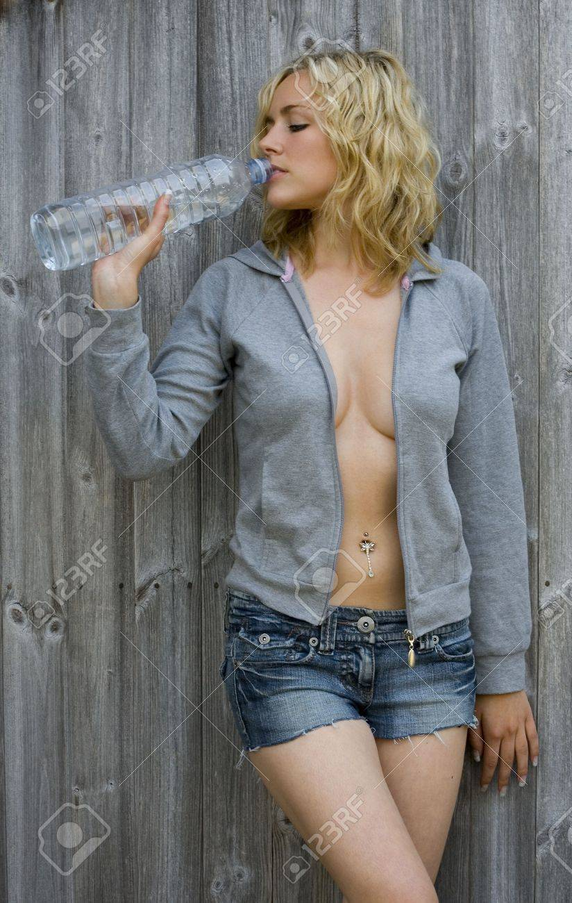 A stunningly beautiful young blond woman drinks from a bottle of water Stock Photo - 1018934