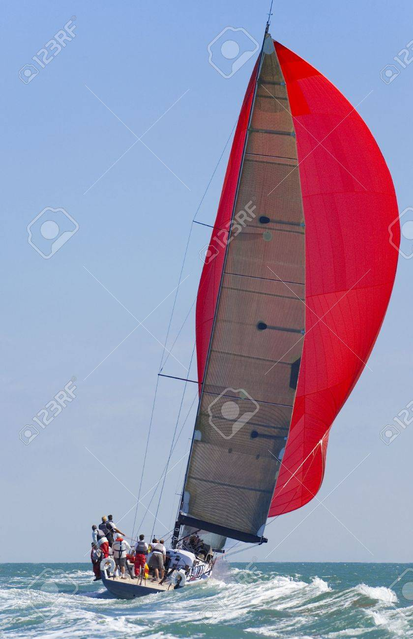 A fully crewed racing yacht with a red spinnaker catching the wind and leaving a big wake Stock Photo - 1080162