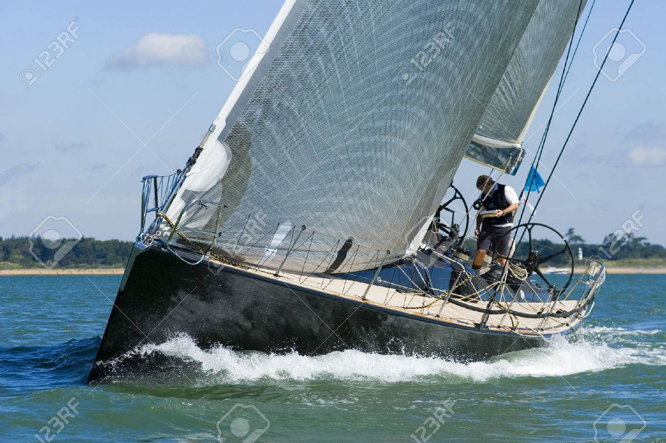 A powerful black racing yacht with wind filled sails powers through coastal waters - 1404475