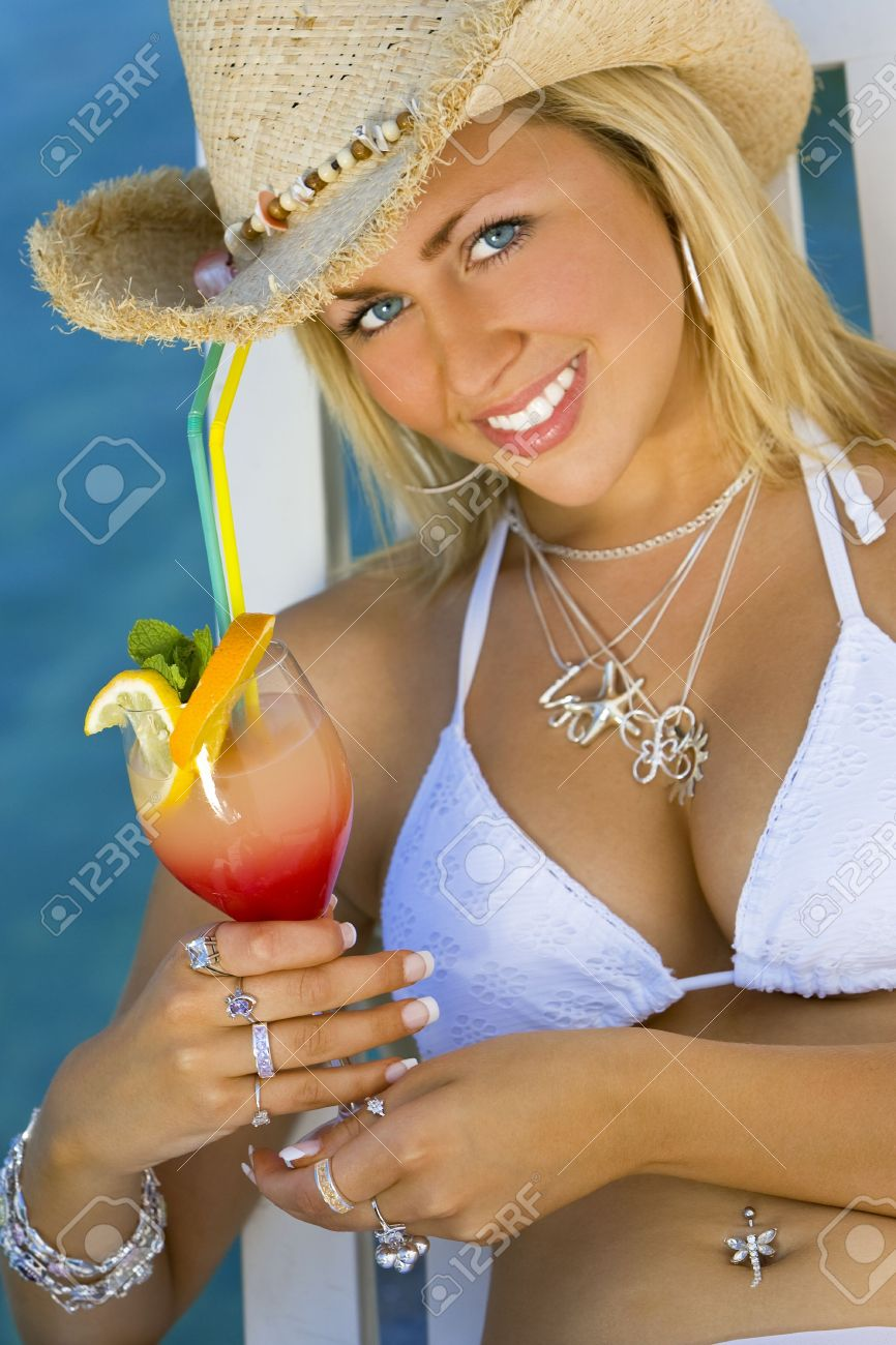 ca9acd9293dec Stock Photo - Stunningly beautiful young blond woman in a straw cowboy hat  and bikini enjoying a cocktail by a deep blue sea