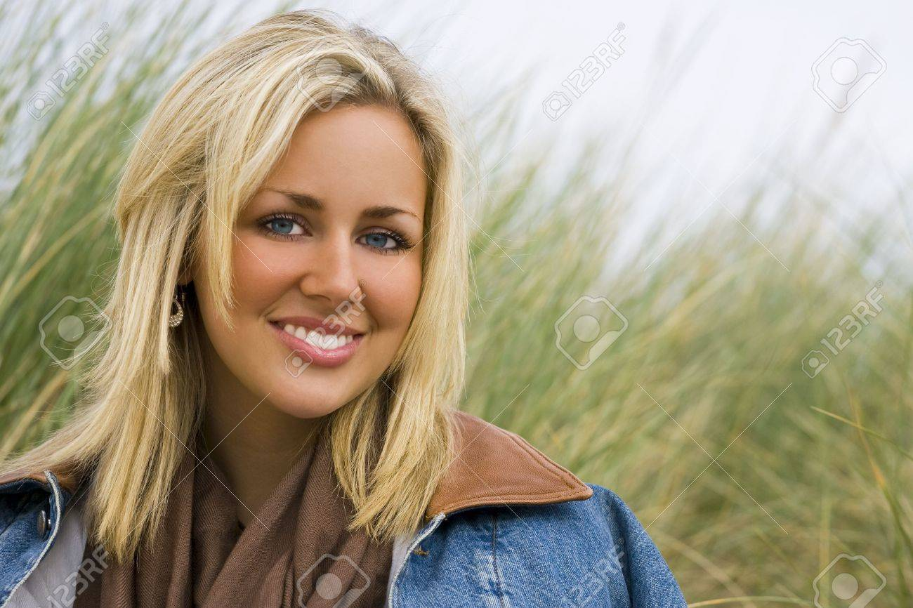 A beautiful young woman wearing a denim jacket sitting and smiling amid tall grass