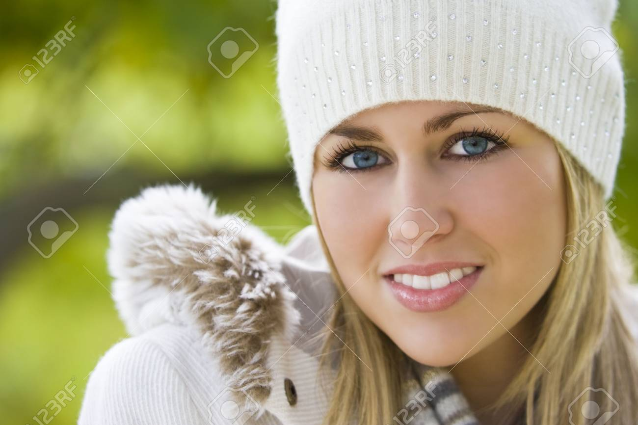A stunningly beautiful young blond woman wrapped up warm smiling and surrounded by beautiful natural colours Stock Photo - 2120253