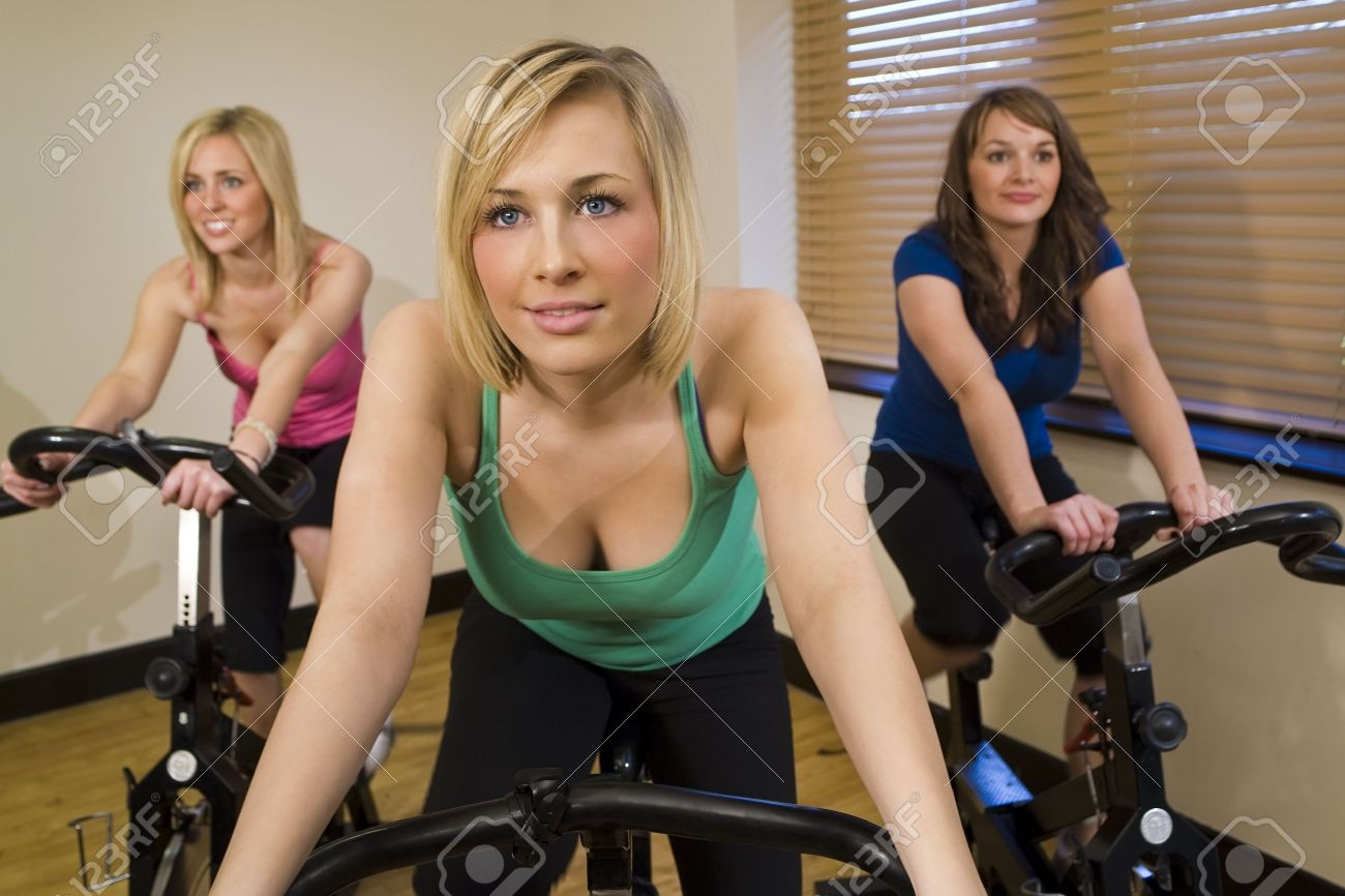 Three beautiful young women working out on spinning bikes at the gym Stock Photo - 2827499