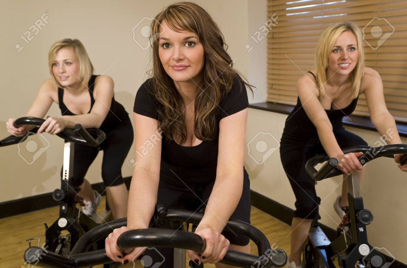 Three beautiful young women working out on spinning bikes at the gym Stock Photo - 2839111