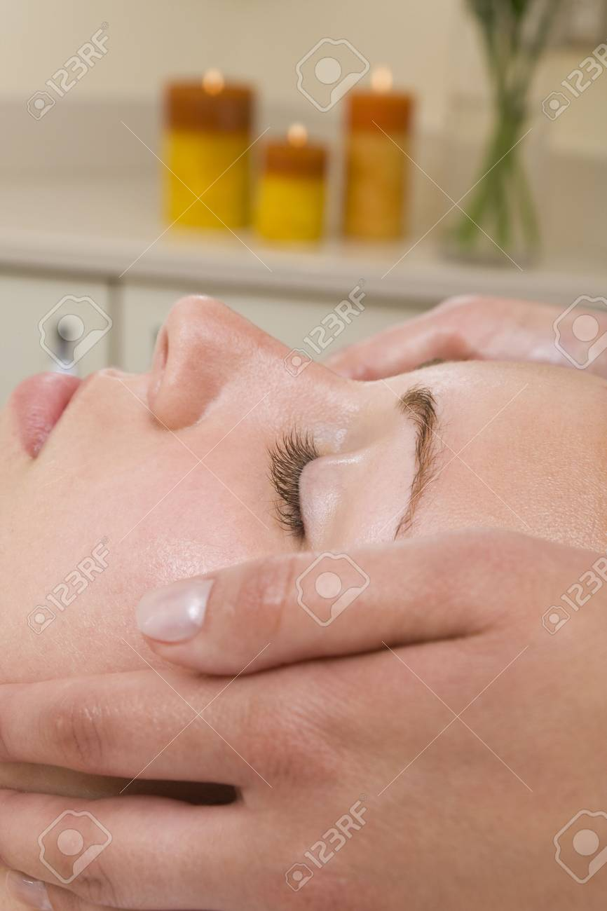 A young woman relaxing at a health spa while having a facial treatment Stock Photo - 3364484