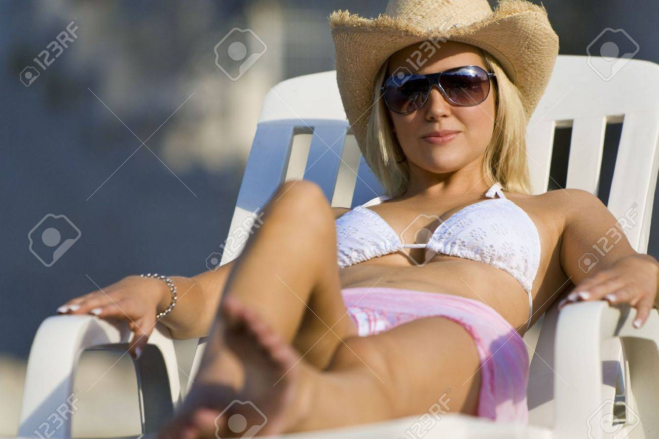 043b6d471b2af A beautiful young blond woman in sunglasses and cowboy hat relaxes in the  sun by the
