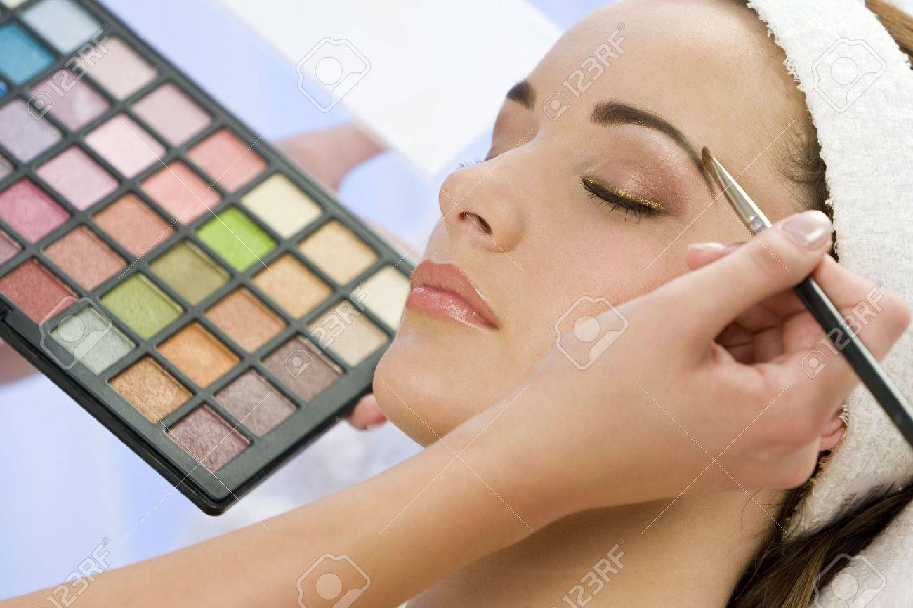 A beautiful young woman having the final touches applied to her make up by a beautician Stock Photo - 3387530