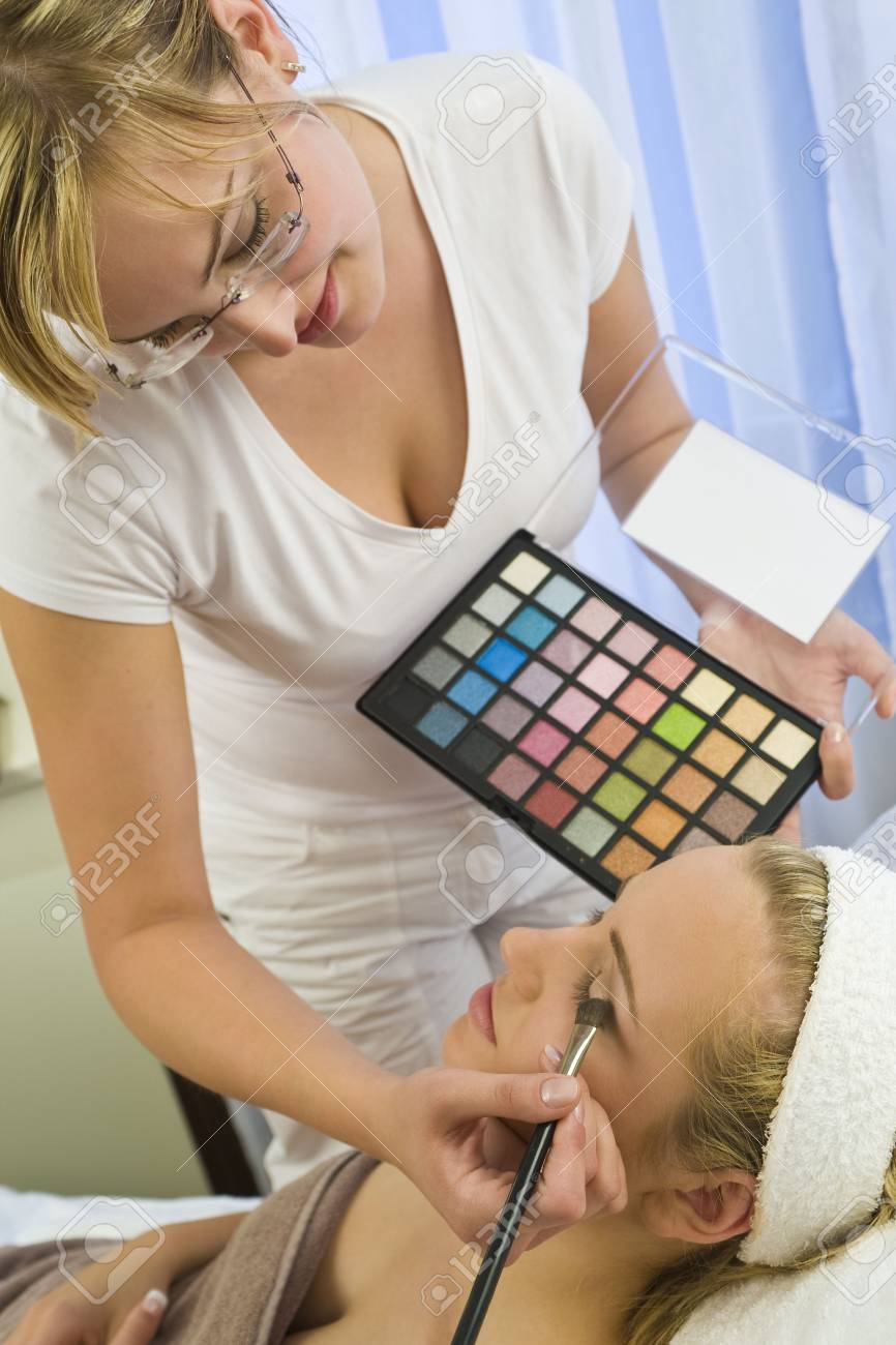 A beautiful young woman having the final touches applied to her make up by a beautician Stock Photo - 3614041