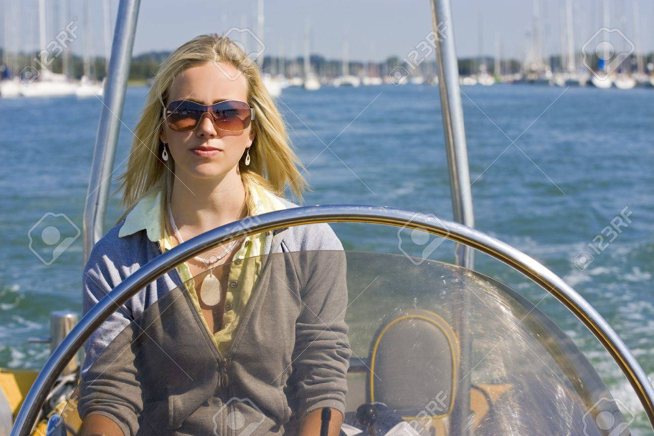 A stunningly beautiful young woman driving a powerboat on a sunny summer day. Stock Photo - 4174730