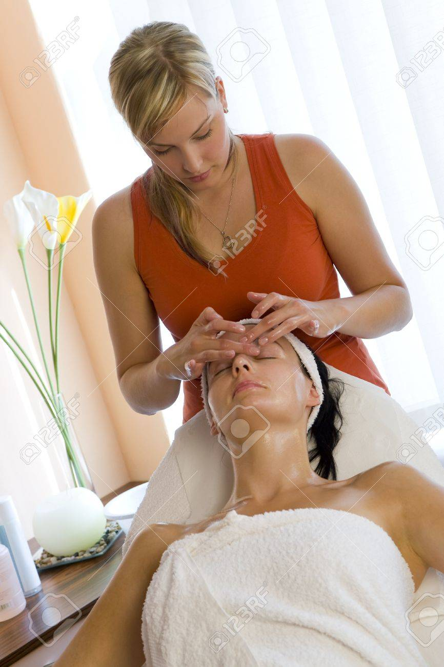 A young woman relaxing at a health spa while having a facial treatment. Stock Photo - 4183968