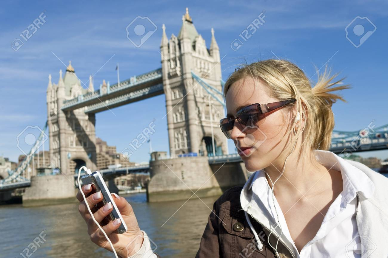 A beautiful young blond woman listening to music on her MP3 player next to the famous Tower Bridge in London, England Stock Photo - 4561669