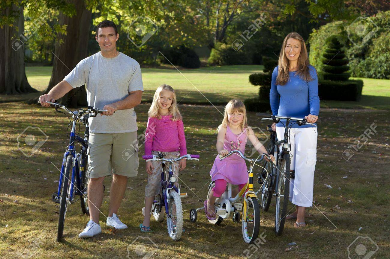 A young family with mother father and two blond daughters riding their bikes in a sun bathed green park Stock Photo - 5620194