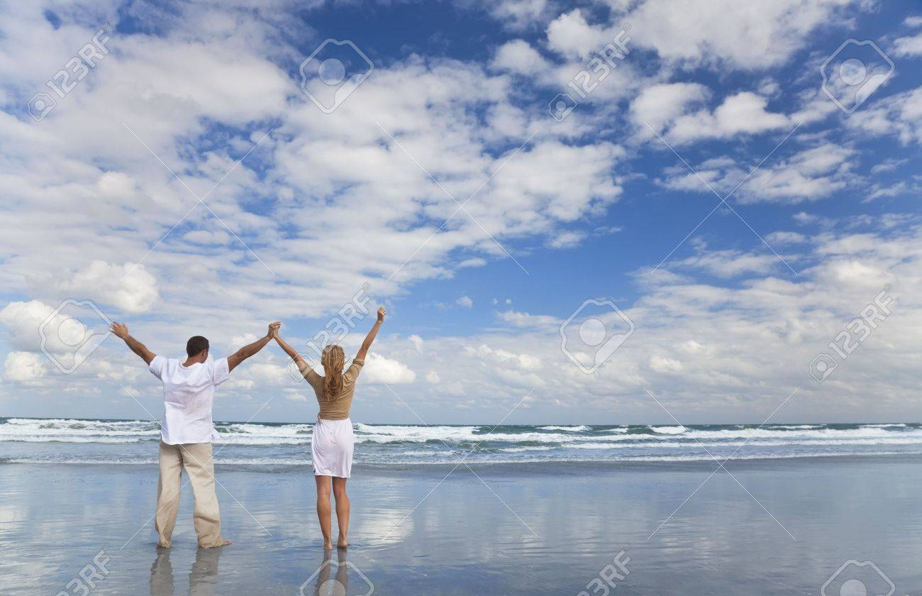 A young man and woman celebrating arms raised and holding hands as a romantic couple on a beach with a bright blue sky Stock Photo - 5796463