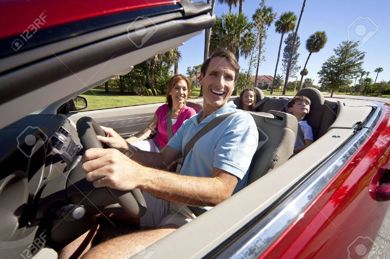 A family of four, mother, father, son and daughter driving in a convertible car on a sunny day in hot location with palm trees Standard-Bild - 5796465