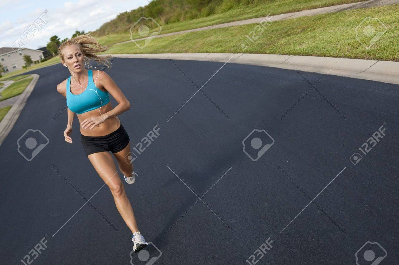 A beautiful fit and healthy blond woman road running while listening to music on her portable mp3 player Stock Photo - 5944626