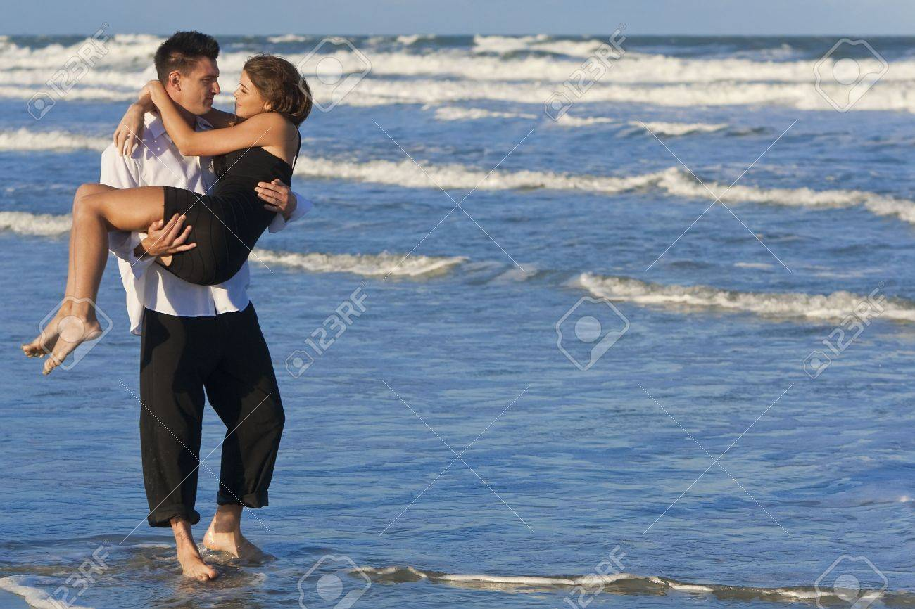 A young man carrying his girlfriend as a romantic couple through the surf on a beautiful beach Stock Photo - 6190128