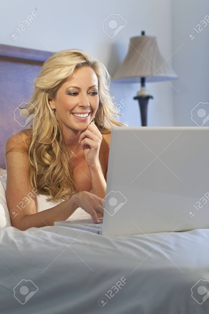 A beautiful happy and smiling young blond woman using her white laptop to surf the internet in bed Stock Photo - 6384971