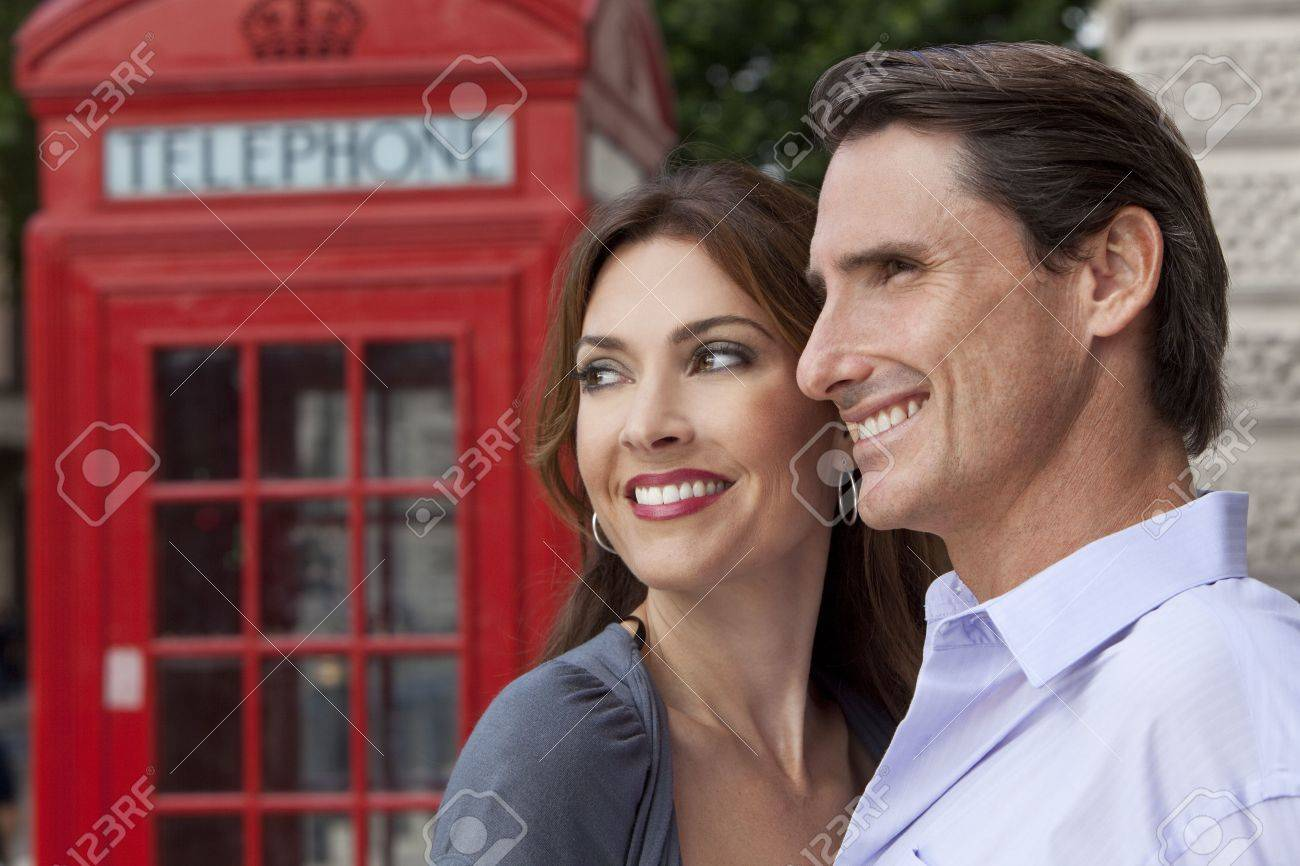 A romantic happy man and woman couple in London, England, with a classic red telephone box out of focus behind him Stock Photo - 7962101