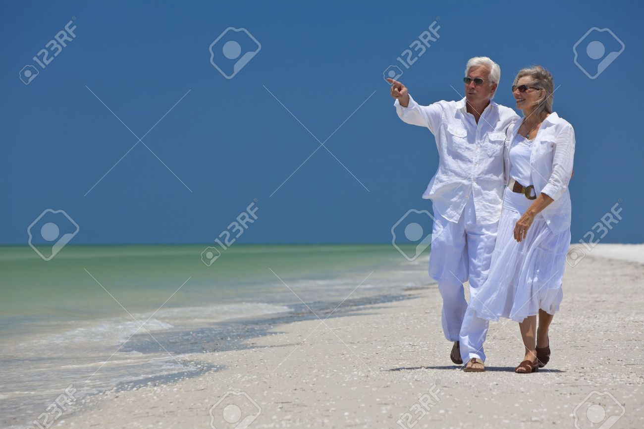 Happy senior man and woman couple walking together looking out to sea on a deserted tropical beach with bright clear blue sky, the man is pointing to the horizon Stock Photo - 8009076