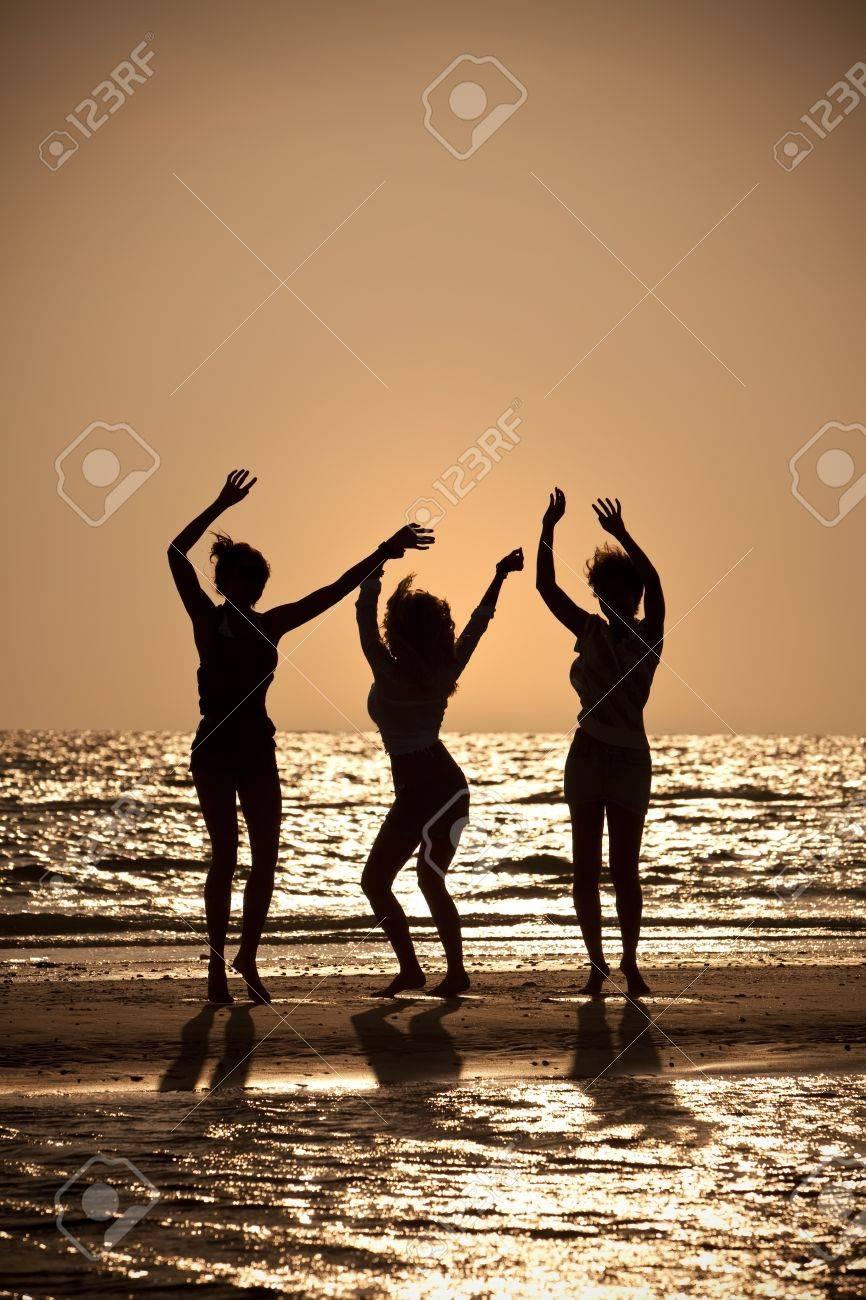 Three beautiful young women in bikinis dancing on a beach at sunset all in silhouette Stock Photo - 8329860