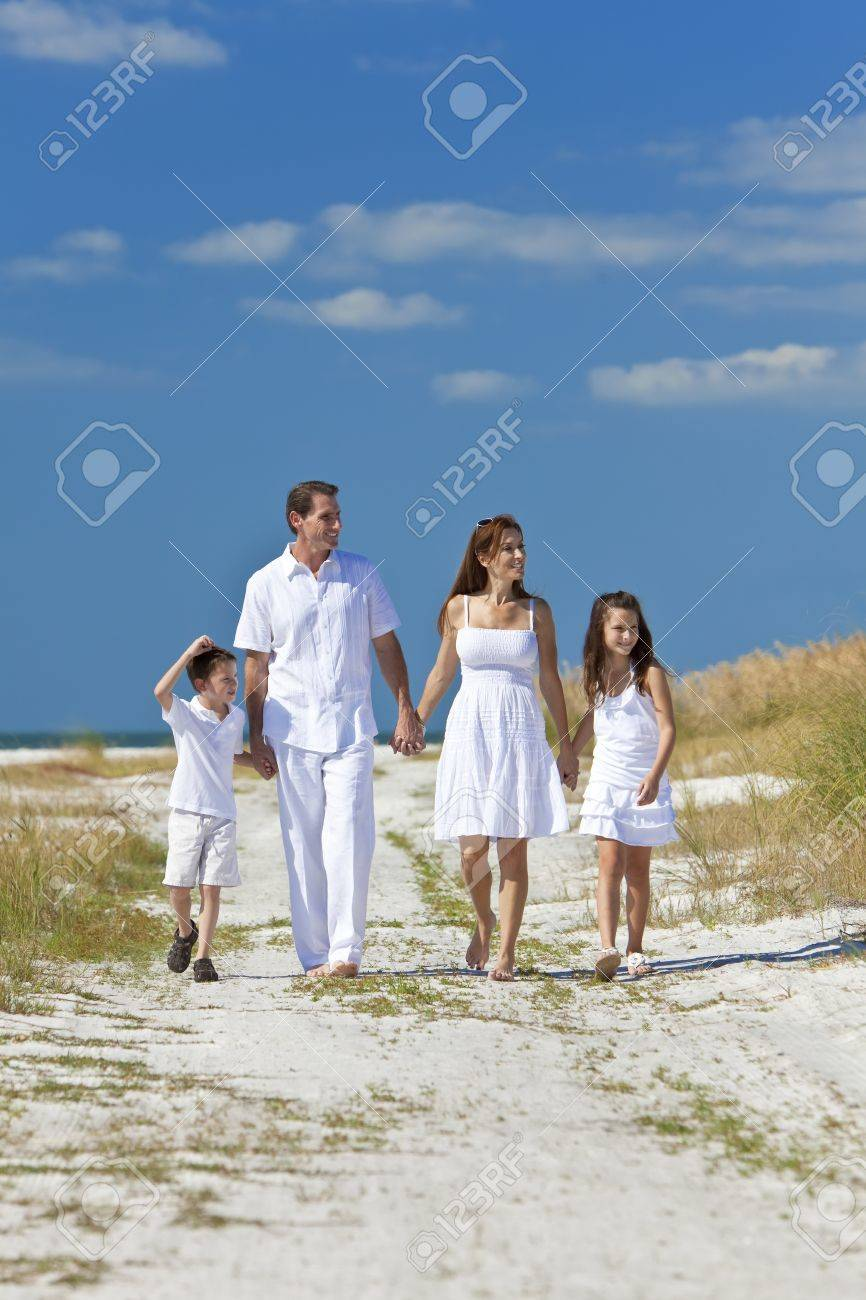 A happy family of mother, father and two children, son and daughter, walking holding hands and having fun in the sand of a sunny beach Stock Photo - 8329890