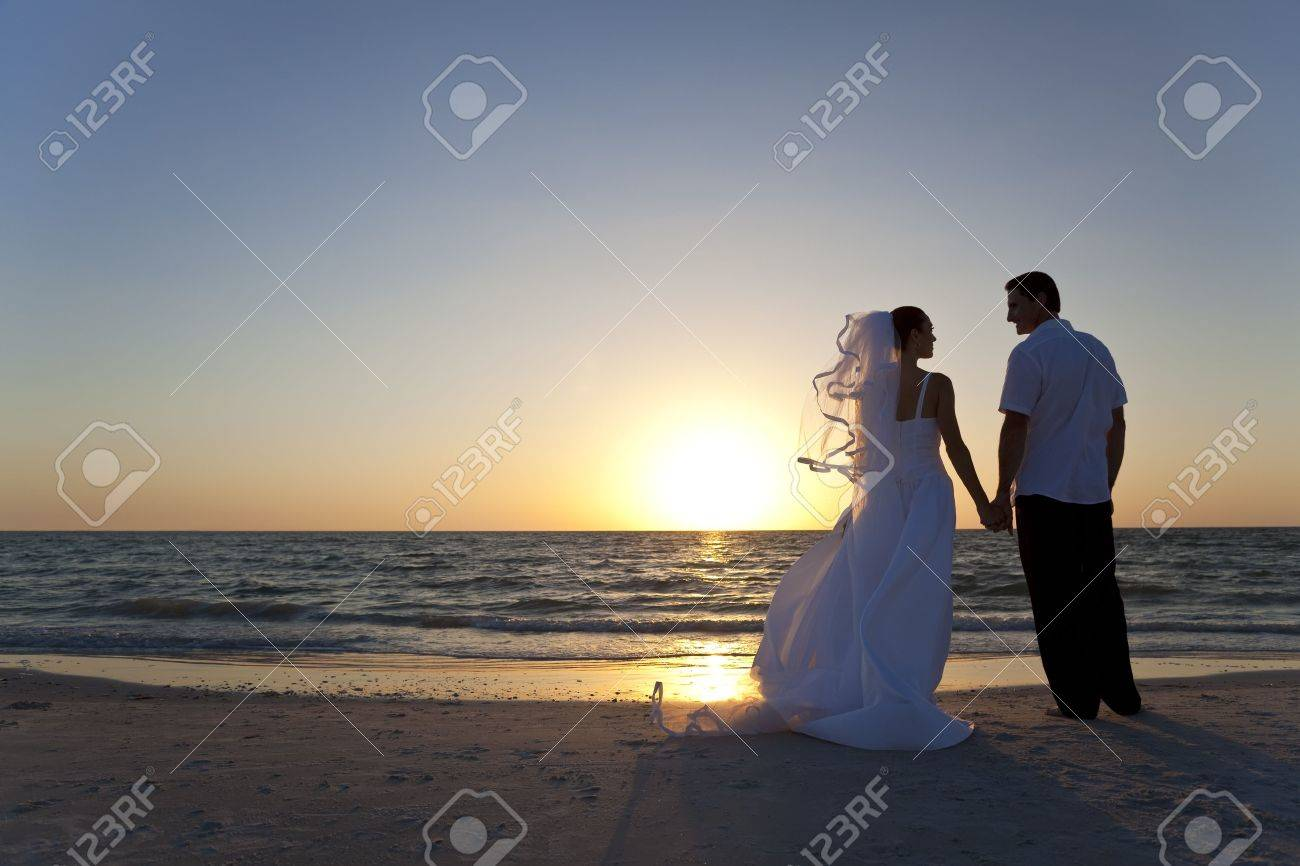 Wedding of a married couple, bride and groom, together at sunset on a beautiful tropical beach Stock Photo - 8806802