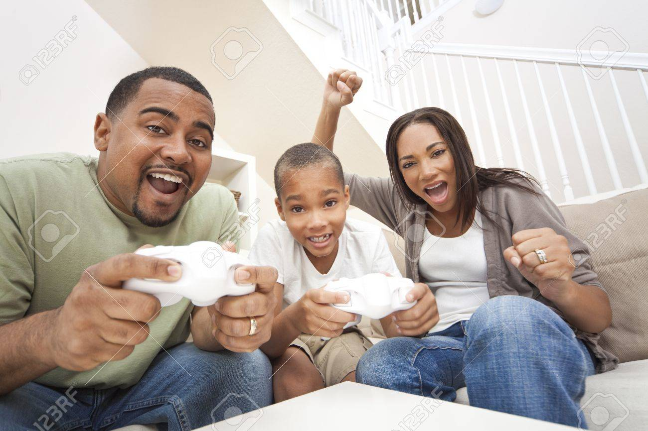 African American family, parents and son, having fun playing computer console games together, Father and son have the handset controllers and the mother is cheering the players. Stock Photo - 9181519