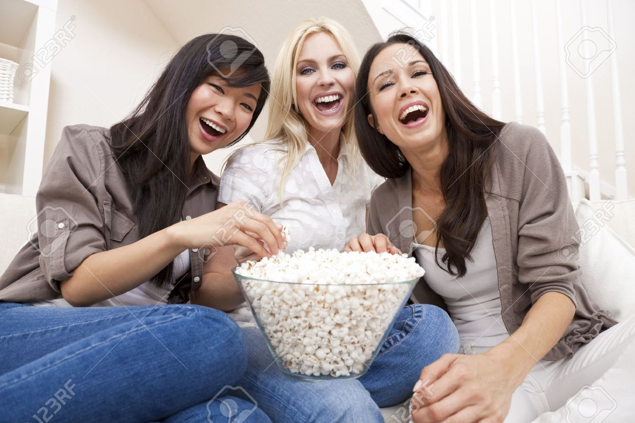 Three beautiful young women friends at home eating popcorn watching a movie together and laughing Stock Photo - 9247042