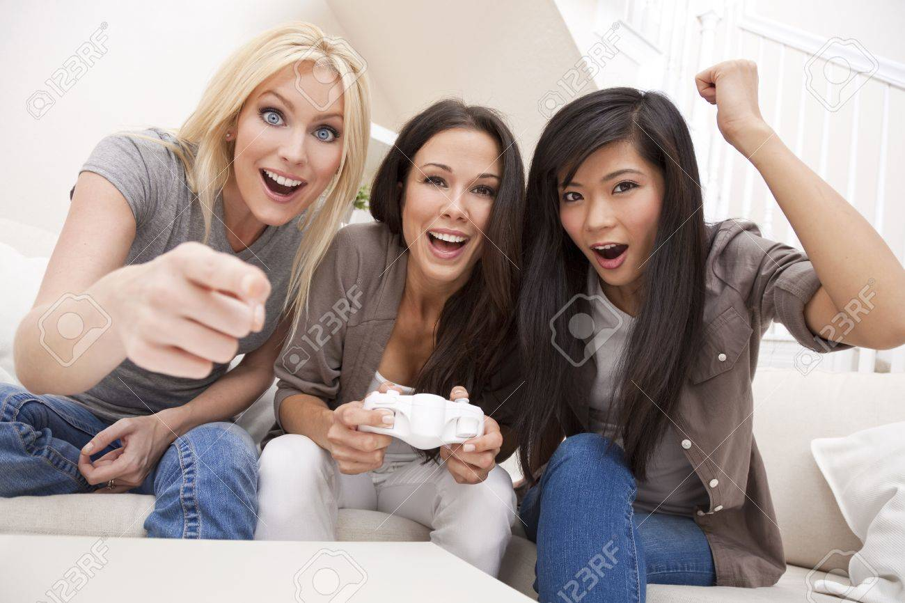Three beautiful interracial young women friends at home having fun playing computer games together and laughing Stock Photo - 9247090