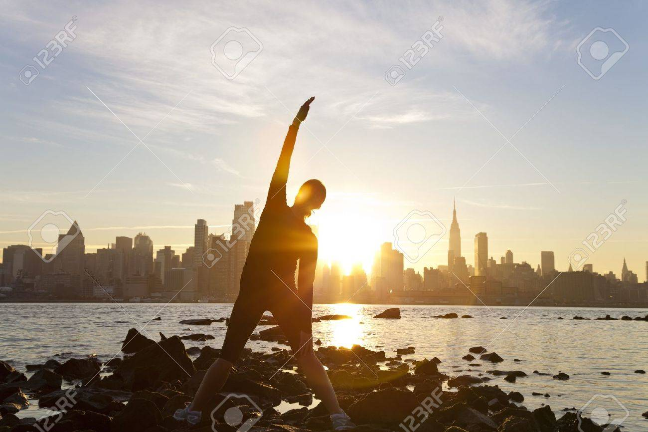 A woman runner stretching in a yoga position in front of the Manhattan skyline, New York City, United States of America, at early morning dawn sunrise Stock Photo - 9360705