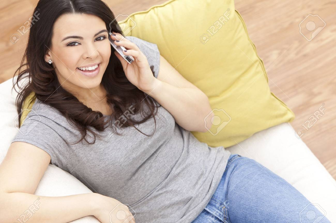 Beautiful happy young Latina Hispanic woman smiling and using her cell phone at home on her sofa Stock Photo - 9952923