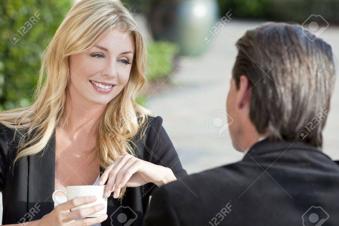 A beautiful and sophisticated young woman having coffee at a modern city cafe table with her friend a smart dressed businessman Stock Photo - 10628920