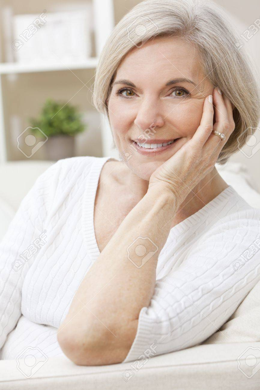 Portrait of an attractive elegant senior woman relaxing at home happy and smiling. Stock Photo - 10628921
