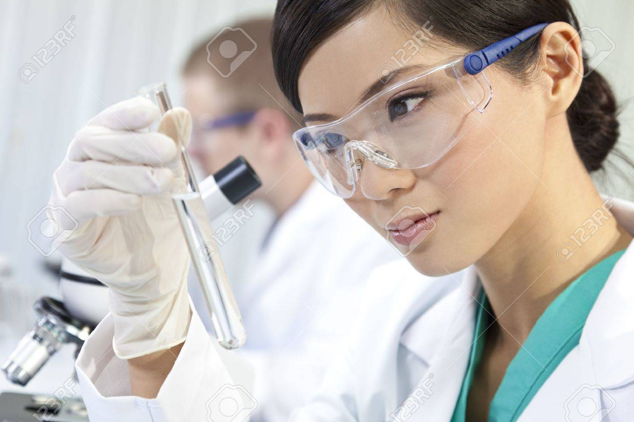A Chinese Asian female medical or scientific researcher or doctor using looking at a test tube of clear liquid in a laboratory with her colleague out of focus behind her. Stock Photo - 11043472