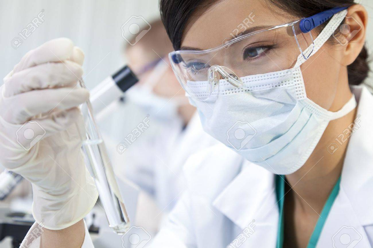 A Chinese Asian female medical or scientific researcher or doctor using looking at a test tube of clear liquid in a laboratory with her colleague out of focus behind her. Stock Photo - 11043471