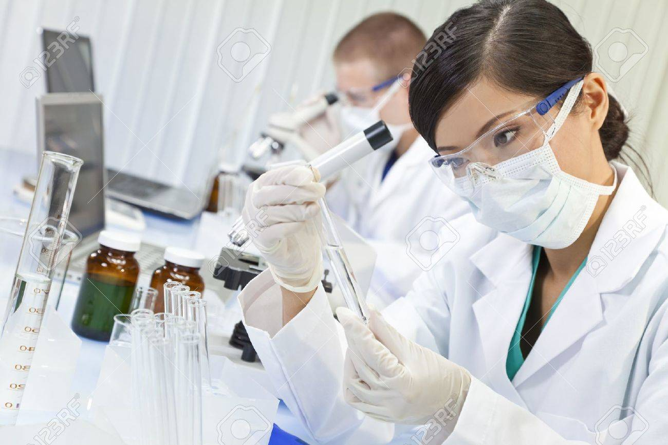 A Chinese Asian female medical or scientific researcher or doctor using looking at a test tube of clear liquid in a laboratory with her colleague out of focus behind her. Stock Photo - 11059175