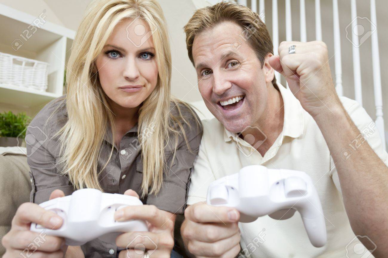 Young married couple, man and woman, having fun playing video console games together. The man has just beaten the woman, he is celebrating, she is unhappy. Stock Photo - 11450397