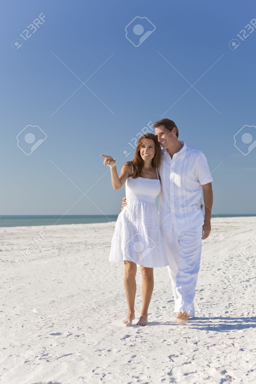 8ea34a77de58 Man and woman romantic couple in white clothes walking on a deserted  tropical beach with bright