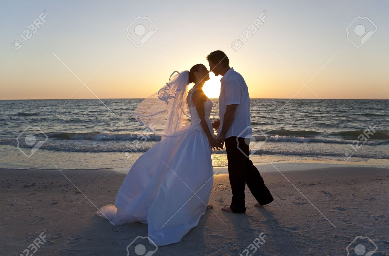 A married couple, bride and groom, kissing at sunset on a beautiful tropical beach - 11450393