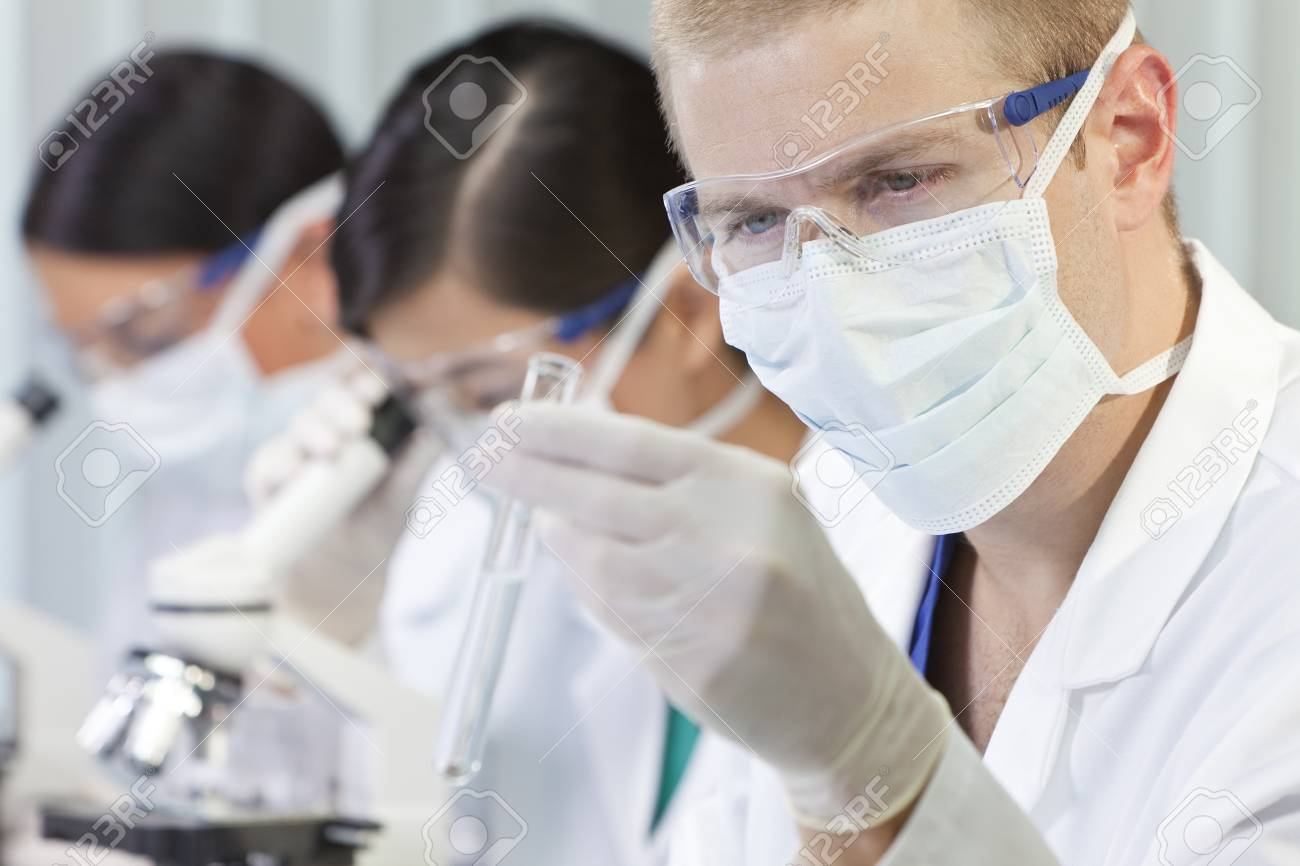 A male medical or scientific researcher or doctor looking at a test tube of clear liquid in a laboratory with microscopes and his female colleagues behind him Stock Photo - 12024391