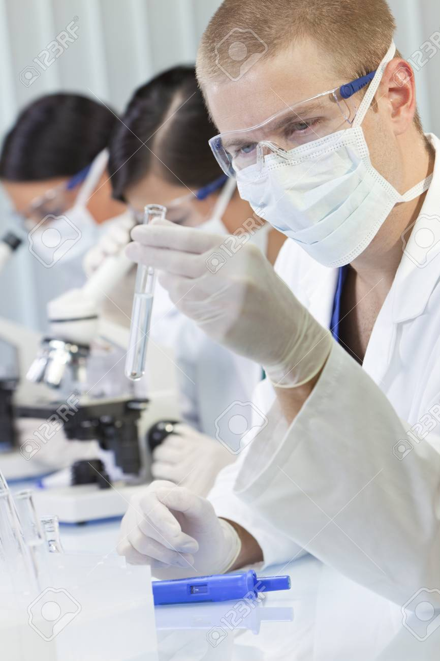 A male medical or scientific researcher or doctor looking at a test tube of clear liquid in a laboratory with microscopes and his female team behind him Stock Photo - 12024397