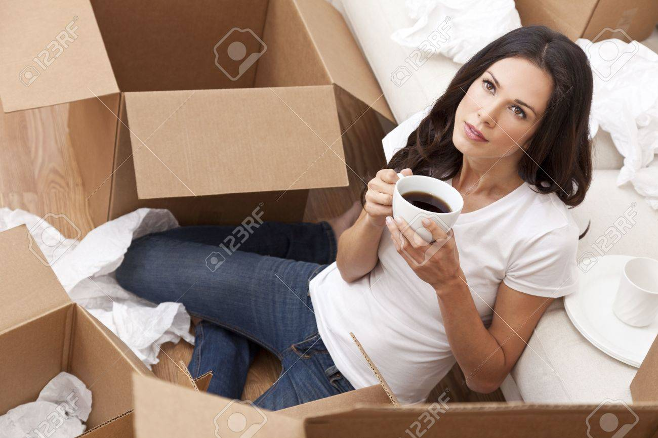 A beautiful single young woman drinking tea or coffee unpacking boxes and moving into a new home. Stock Photo - 12083976