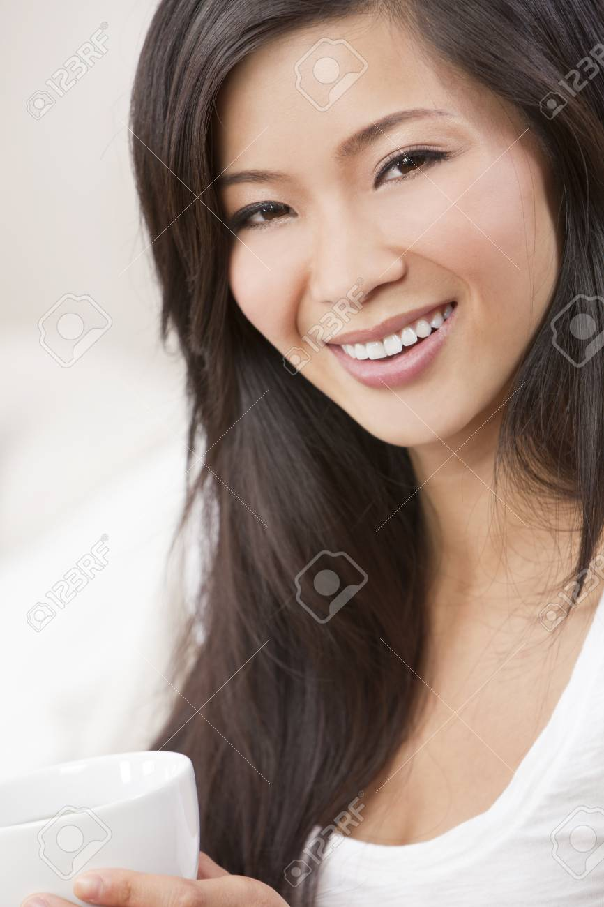 A beautiful young Chinese Asian Oriental woman with a wonderful toothy smile drinking tea or coffee from a white cup Stock Photo - 12328905