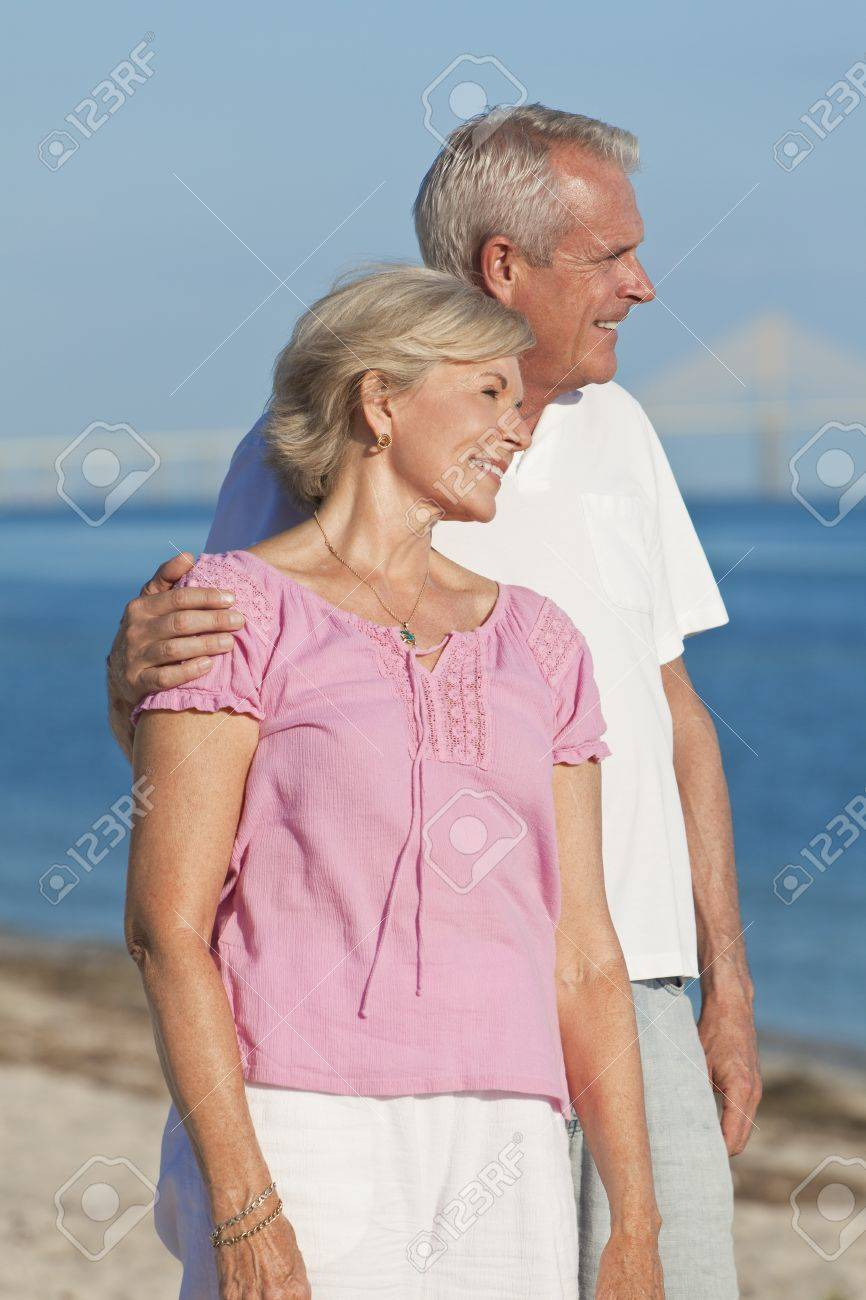 Happy senior man and woman couple together embracing and walking on a deserted tropical beach with a bridge in the background Stock Photo - 12328917