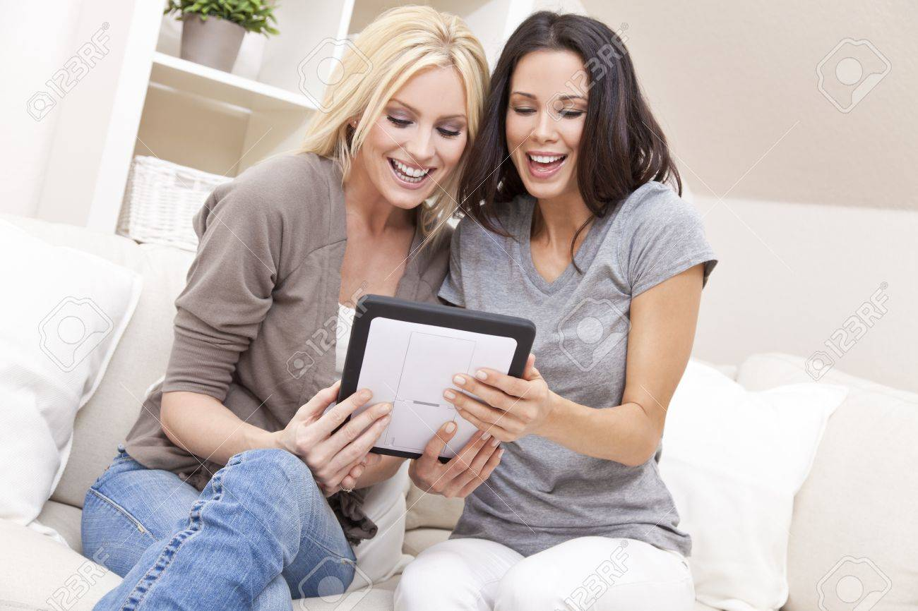 Overhead photograph of two beautiful young women at home sitting on sofa or settee using a tablet PC computer and laughing Stock Photo - 12328943