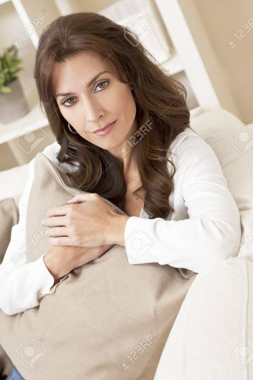 Indoor portrait of a beautiful young brunette woman in her thirties or forties holding a cushion and looking thoughtful Stock Photo - 12813689