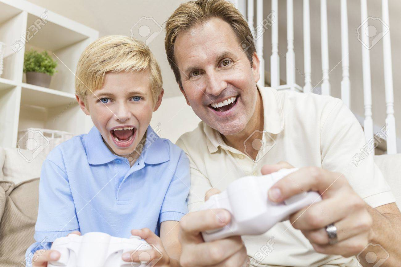 Happy family, man and boy, father, son, having fun playing video console games together Stock Photo - 14748007