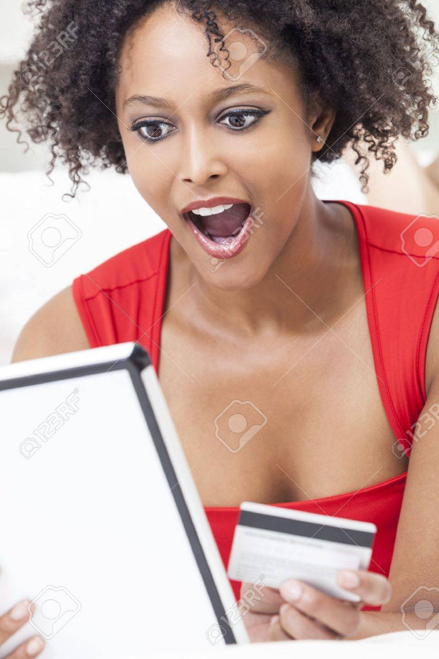 A beautiful, happy and surprised, mixed race African American girl or young woman laying down wearing a red dress using a tablet computer and credit card internet shopping on line Stock Photo - 15587499